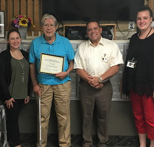 """Dominican Village resident Henry """"Hank"""" Fairchild receiving a certificate in honor and appreciation of submitting artwork in the 2018 Art from the Heart program."""